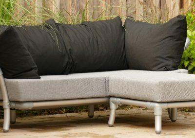 loungebank voor in de tuin met licht grijze en zwarte kussens