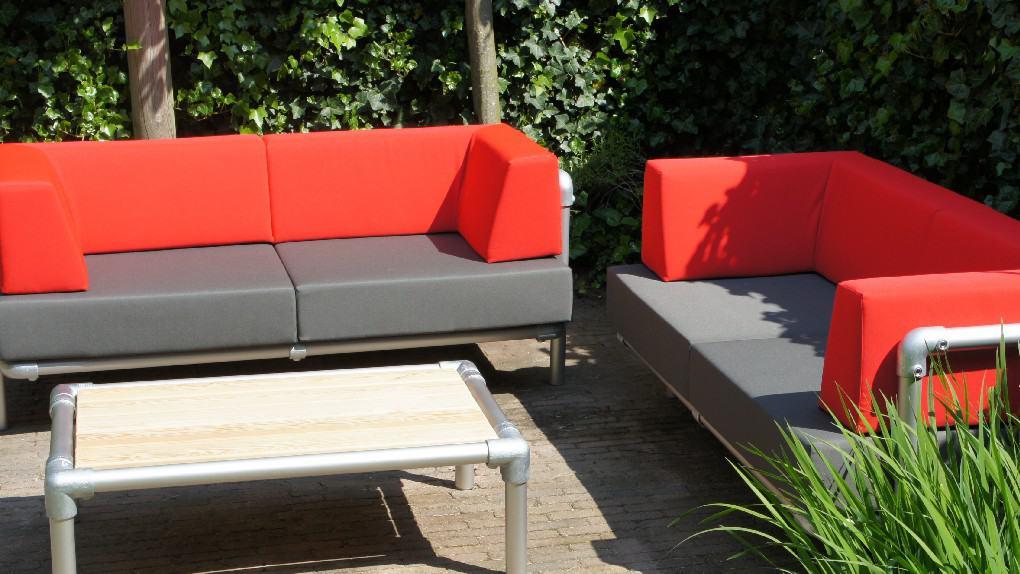 2 loungebanken die samen een lounge hoekbank vormen in de tuin. Strak gestoffeerd in antraciet grijs en rode buiten stof