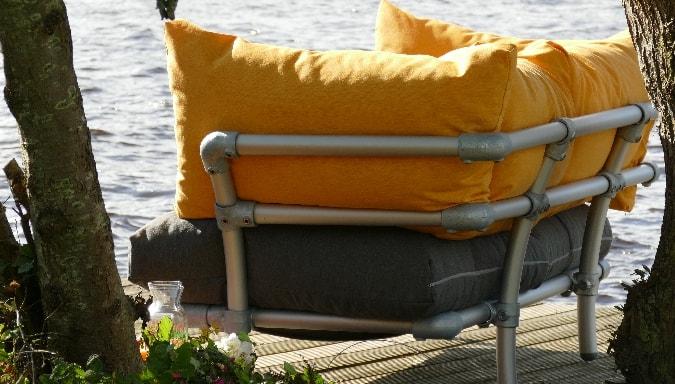 loungebank met gele kussens op terras