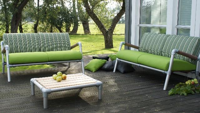 design loungebank uitgevoerd als loungeset met groene bolgevormde zitkussens en groen gestreepte rugkussens voor in de tuin