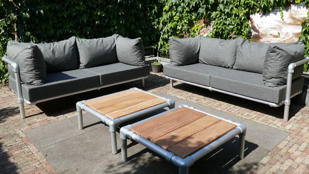 lounge tuinmeubelen neergezet als twee loungebank buiten in de kleur antraciet grijs
