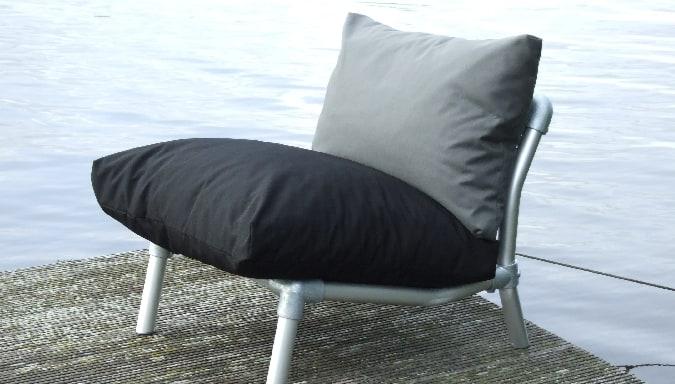 lounge stoel voor op terras met losse plof kussens in zwart en antraciet grijs
