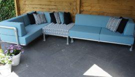 hoek loungebank voor buiten in de tuin met strakke kussens in licht blauw