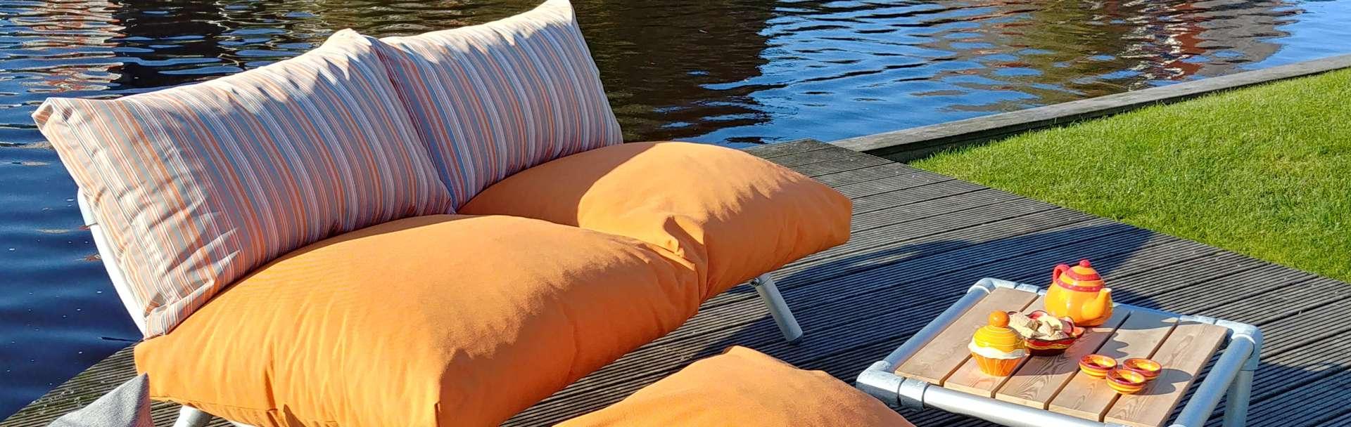 loungebank voor buiten in de tuin met los gevulde kussens in de kleur oranje