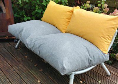 loungebank voor in de tuin met los gevulde kussens in grijs en geel